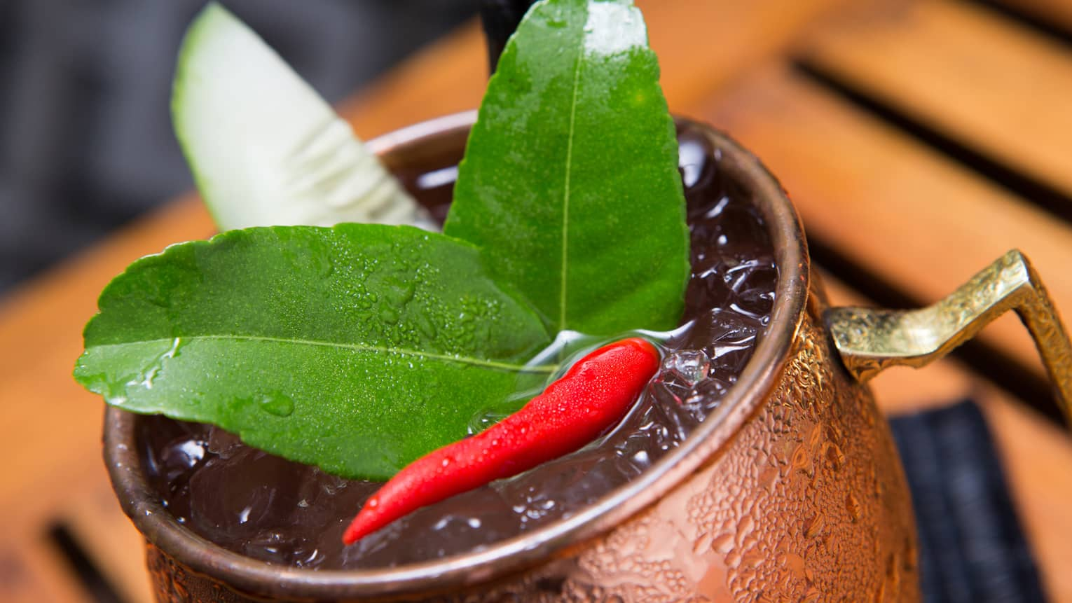 Close-up of green lime leaves, small red hot pepper on cocktail in brass cup