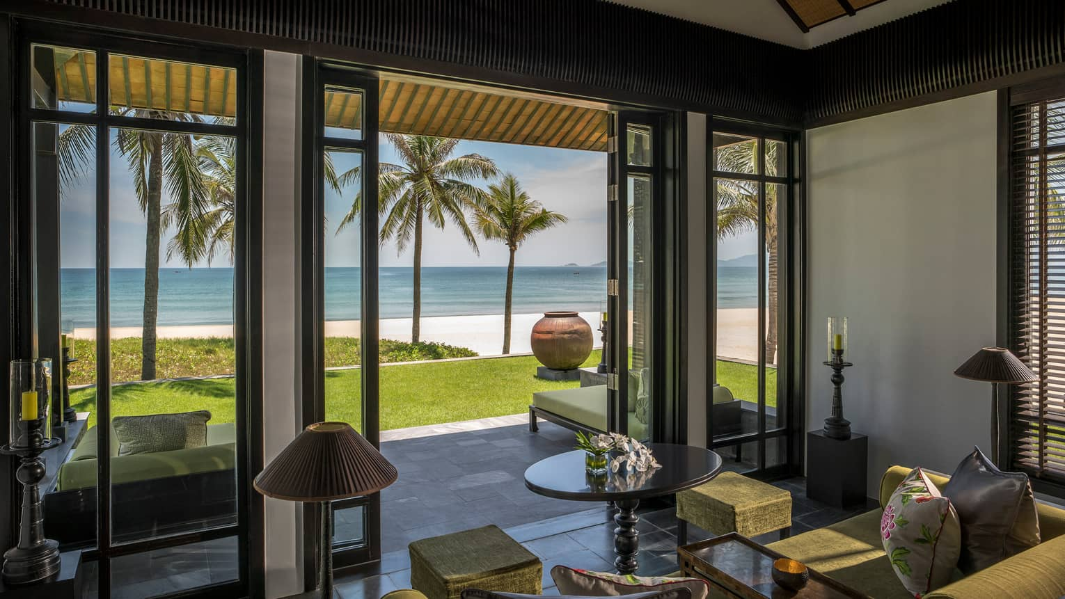 Beachfront Villa living room with open walls to lawn, palm trees, beach, ocean