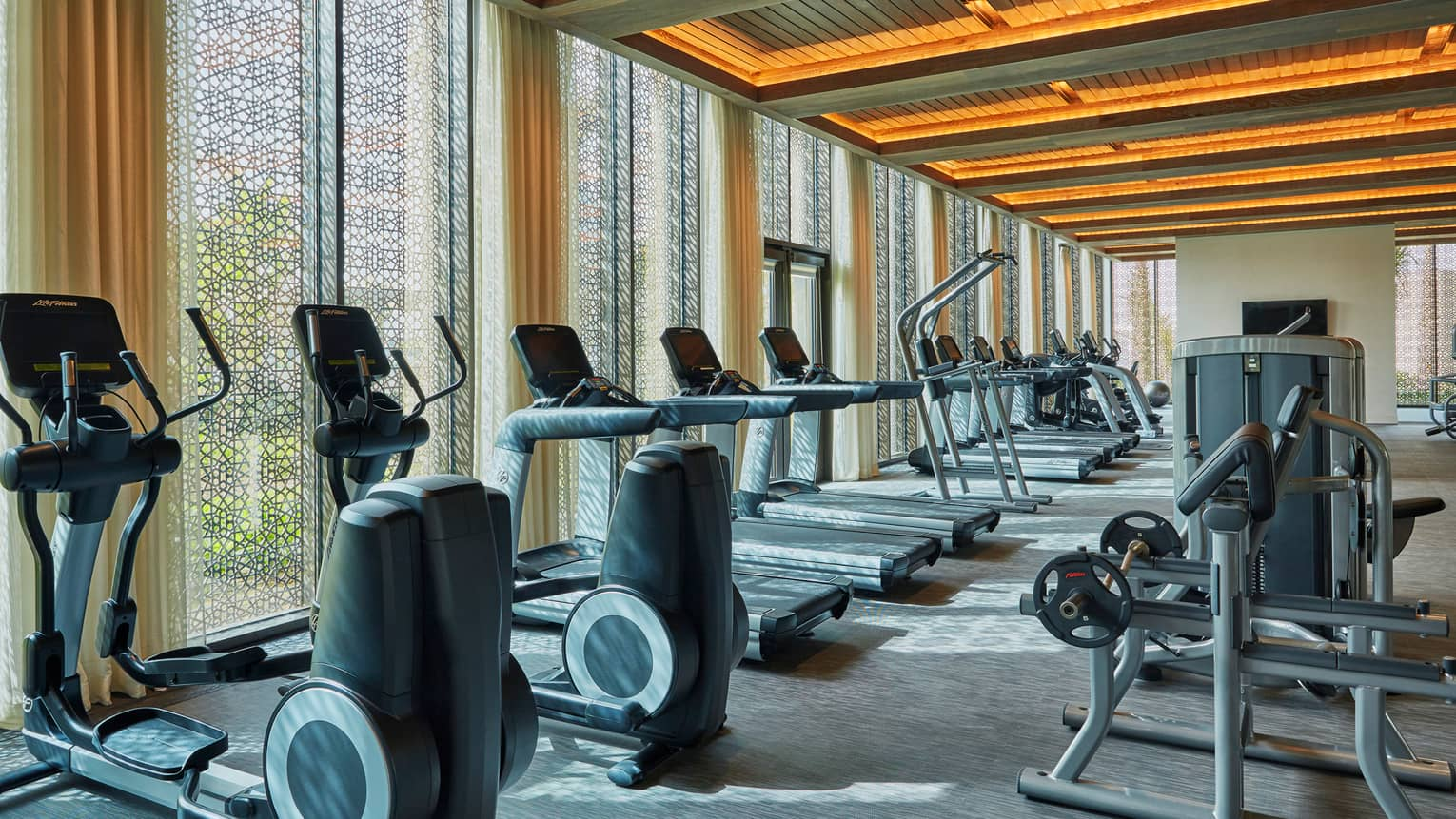 Fitness Centre cardio machine lined up against window with screen, recessed wood beam ceilings with orange lights
