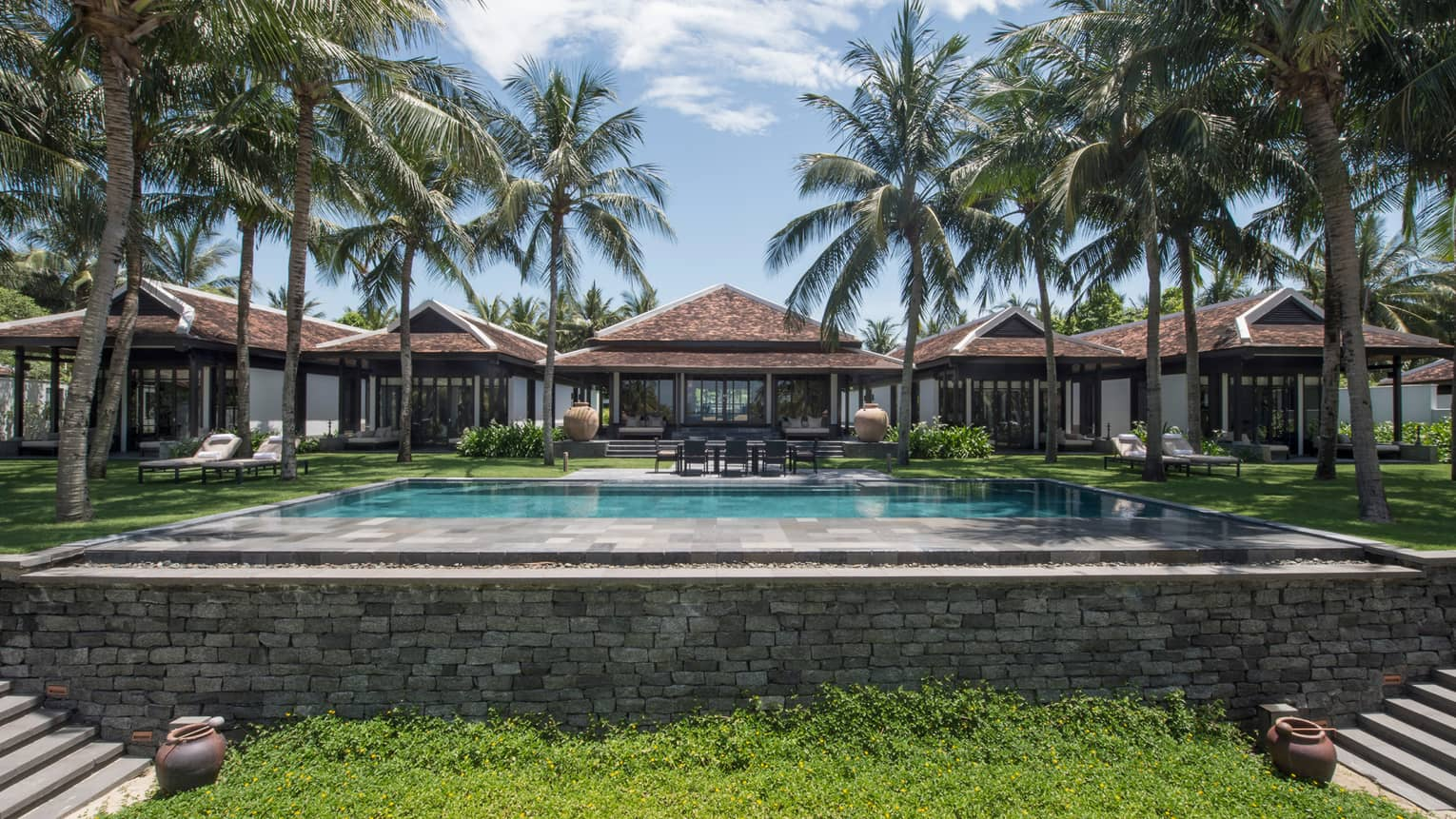 Ocean-View Villas behind large stone outdoor swimming pool, tall palm trees