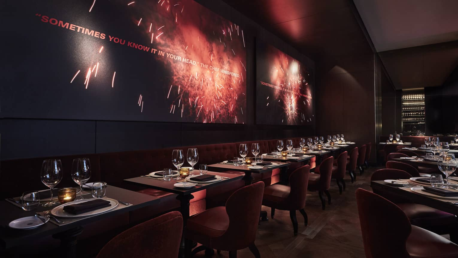 Rows of dining tables lined with red velvet chairs under paintings of fireworks in CUT dining room