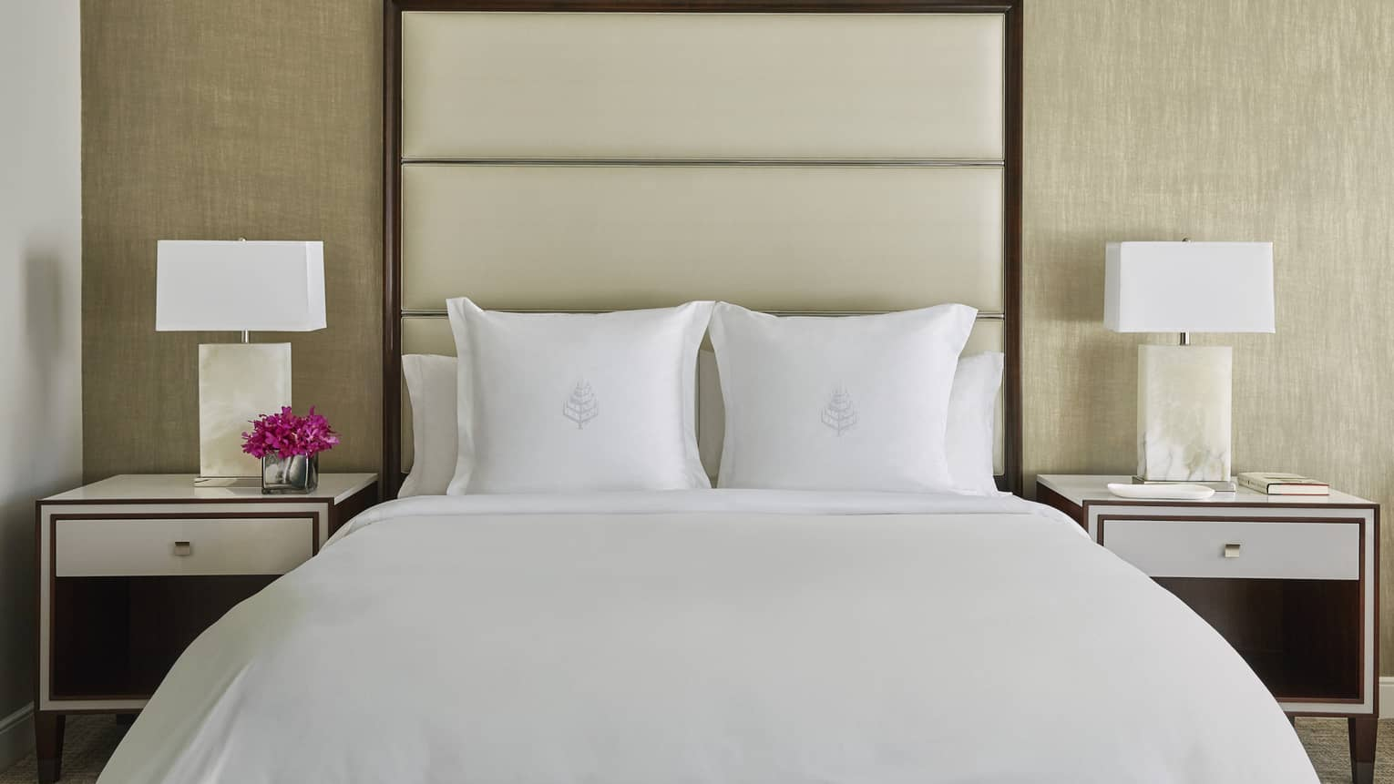 Deluxe Accessible Room head-on view of bed with white linens, tall padded beige headboard, nightstands with lamps