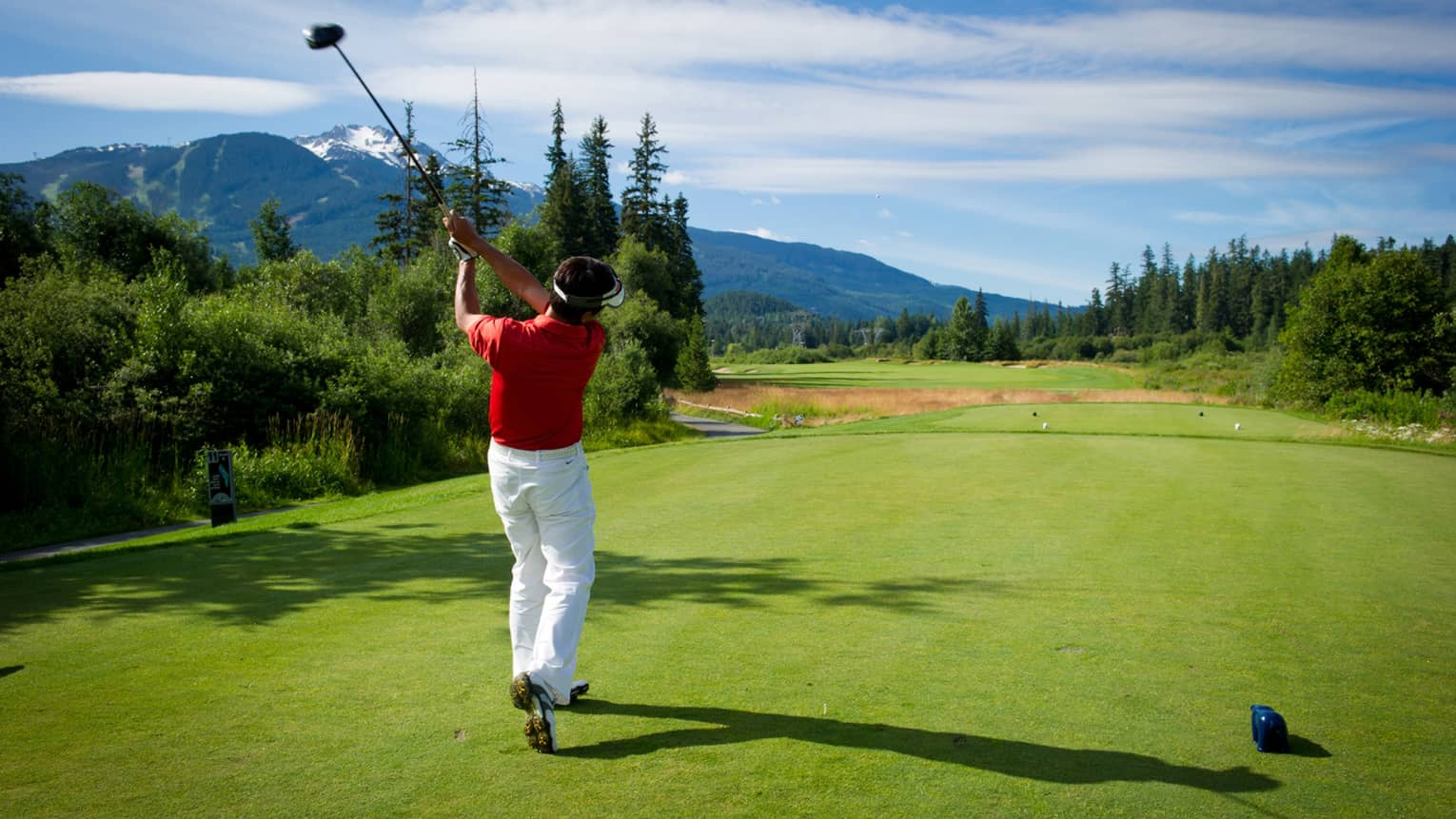 Back view of man swinging golf club on green, mountains in distance