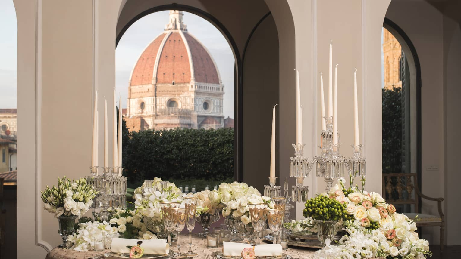 White roses, flowers on elegant banquet table under pillows, Duomo views