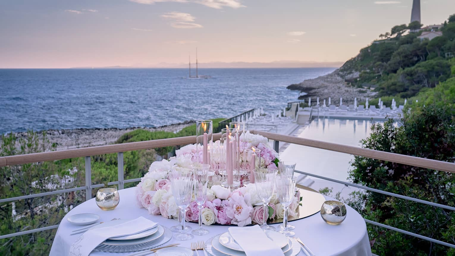 Balcony with round set table, pink floral arrangement, water views at sunset