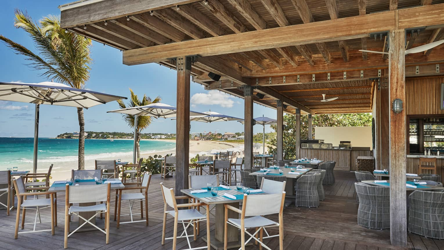 Bamboo restaurant outdoor patio, tables and chairs under wood pergola, beside sunny beach