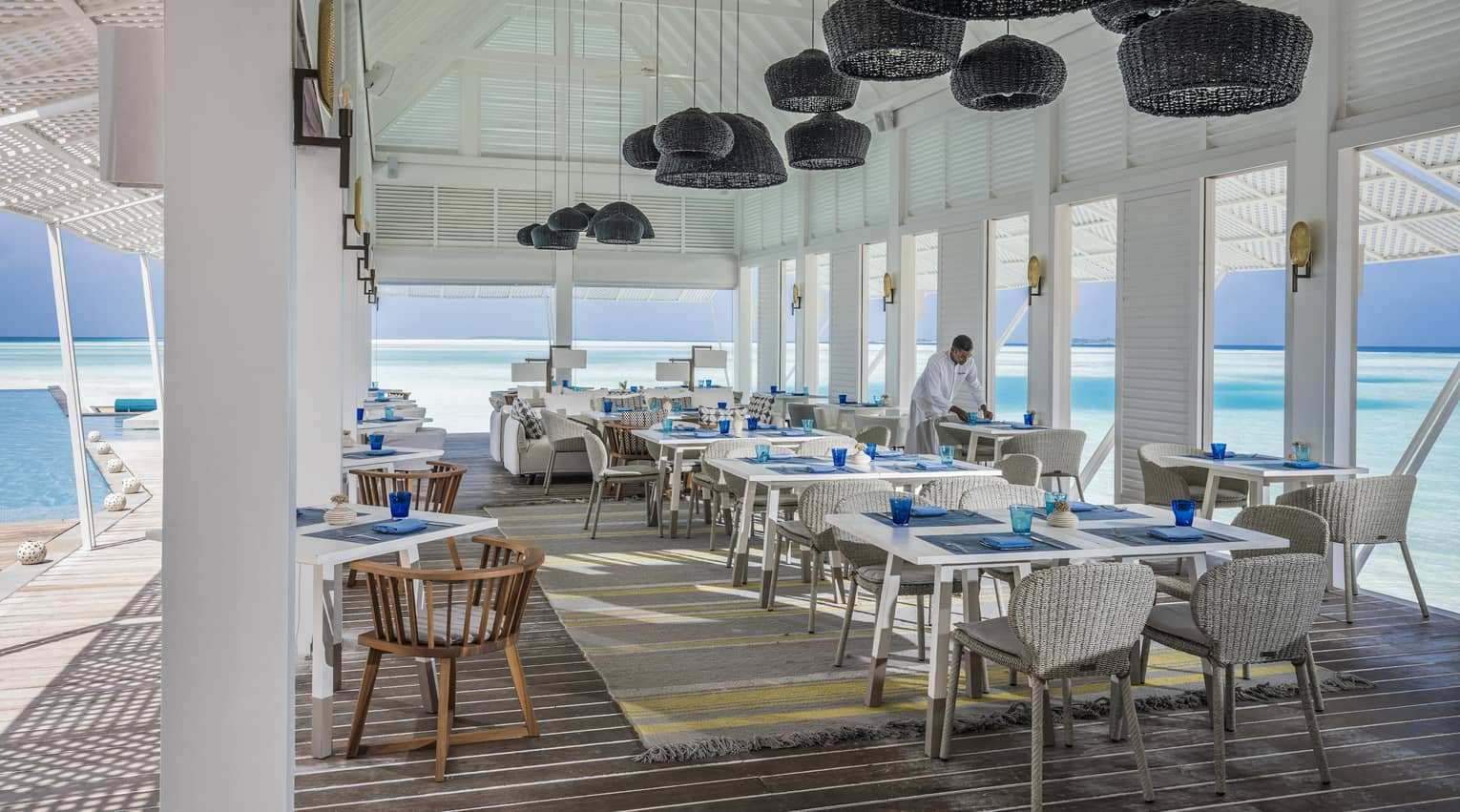Wicker lanterns hang above clean place-settings adjacent to the ocean at the Blu Beach Club