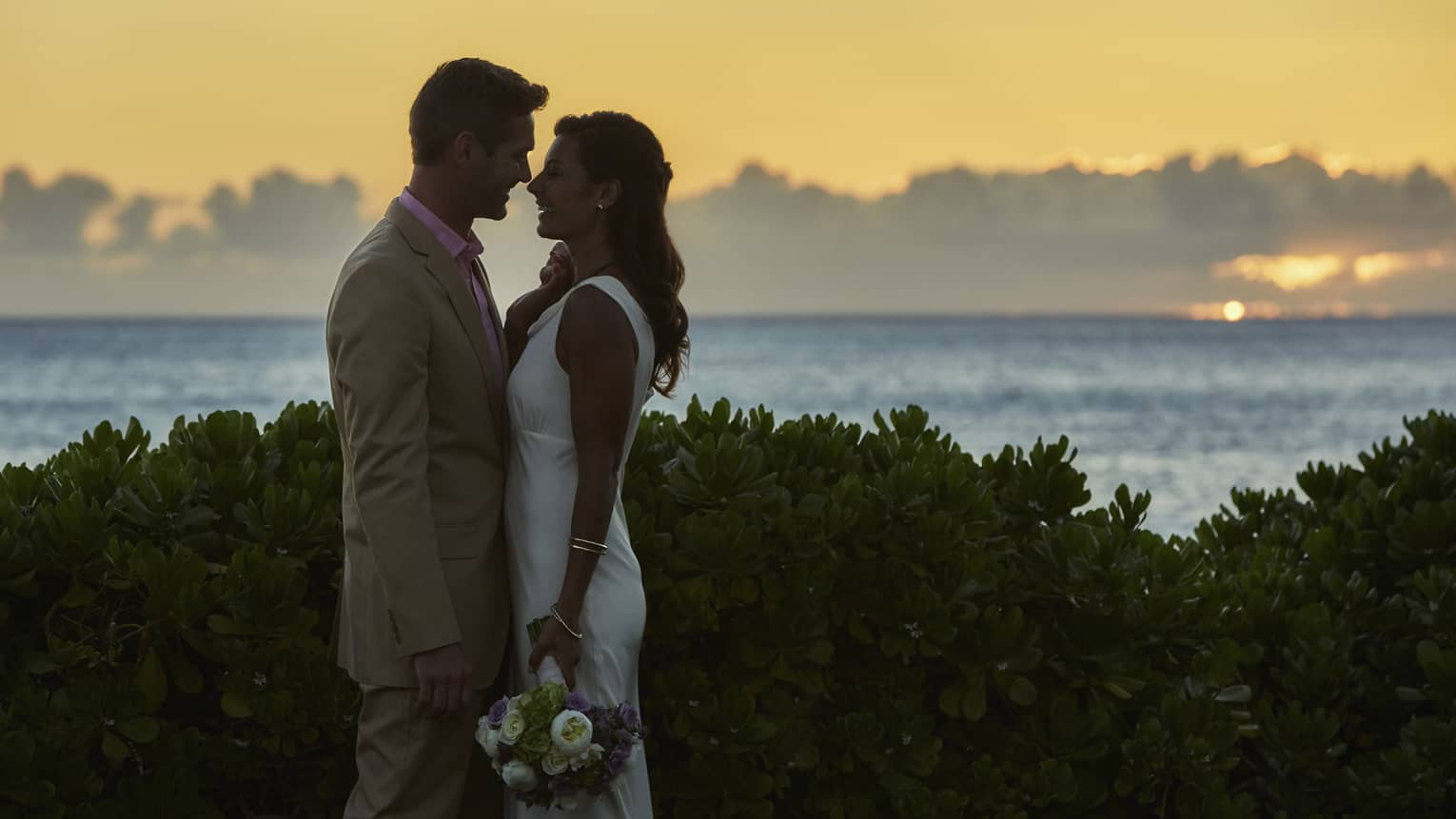 Silhouettes of bride and groom leaning in for kiss against sunset