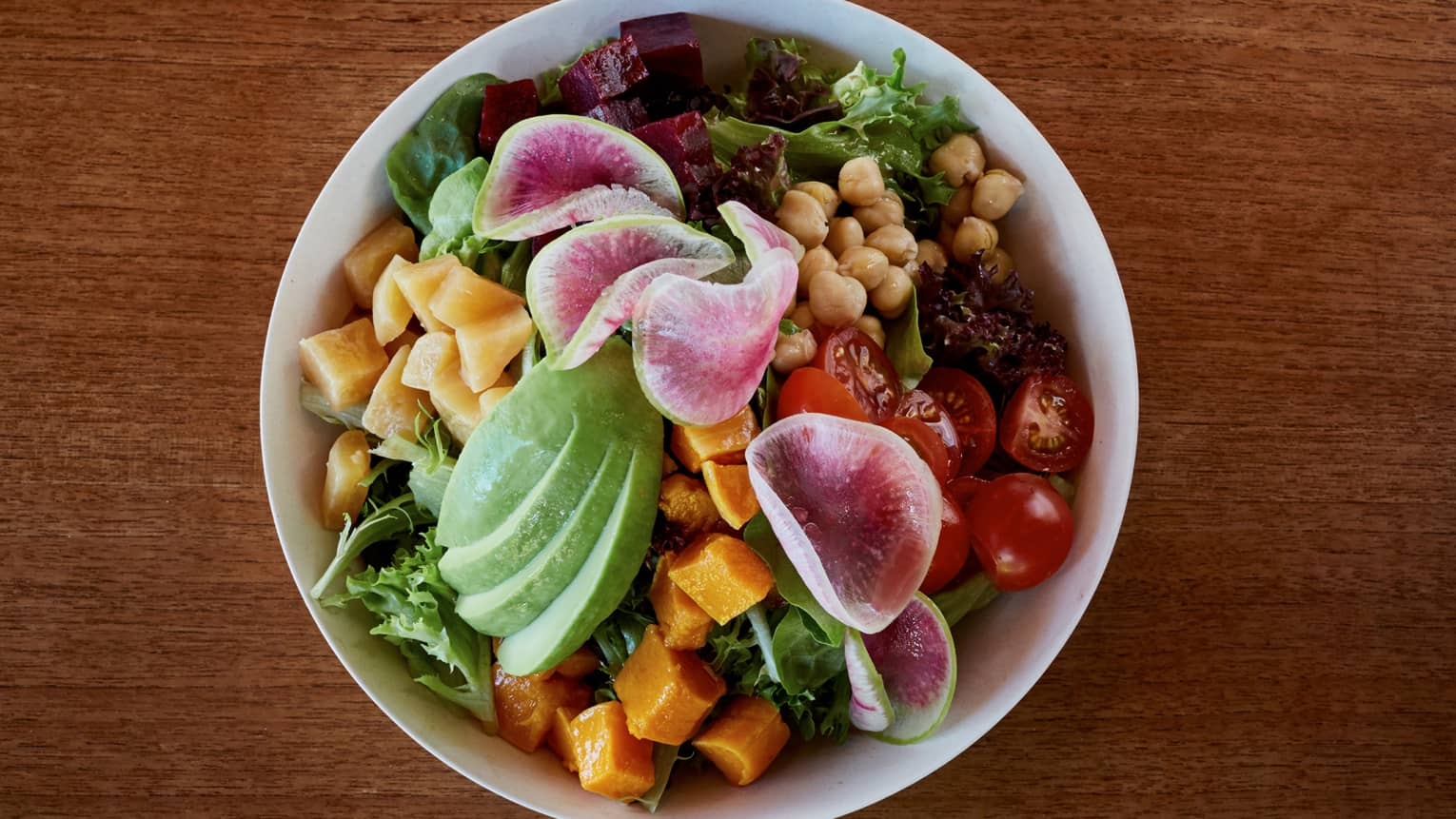 Aerial view of bowl with fresh chopped greens, vegetables, avocado slices, chickpeas
