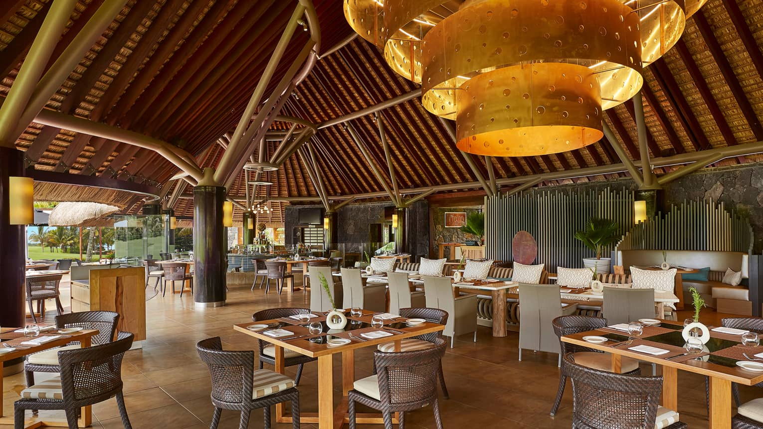 Modern gold lamp under bamboo thatched roof over Il Forno open-air dining room