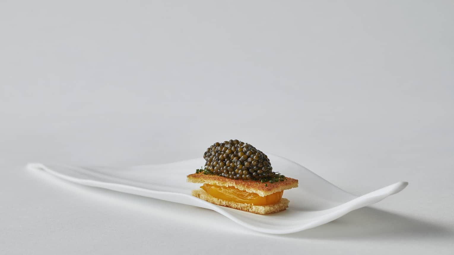 Two crackers with orange filling in between topped with caviar