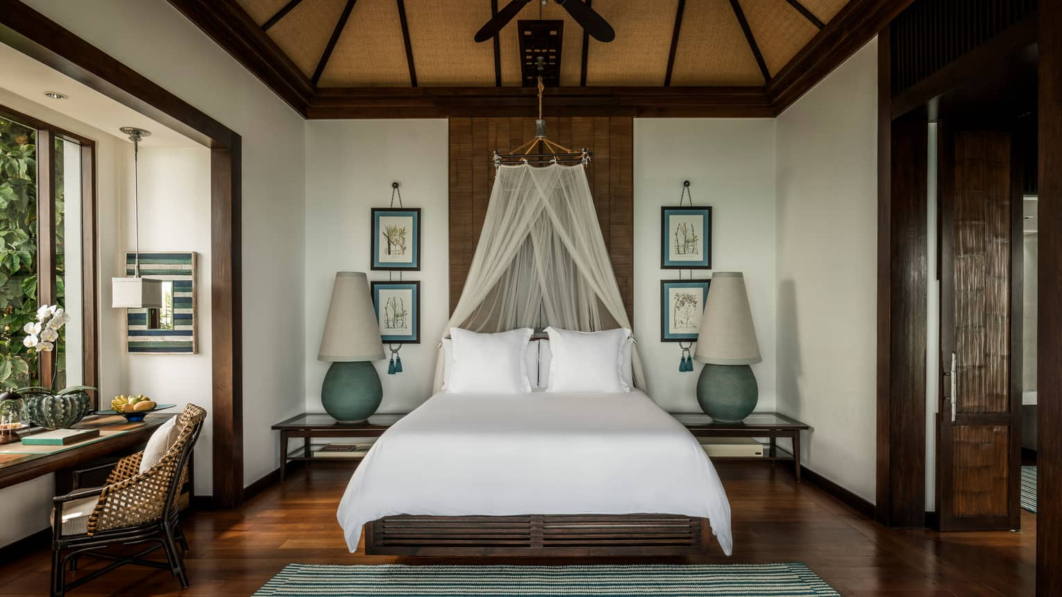 Family Pool Villa bed with white net canopy, large lamps on each side, wood floors, desk by window