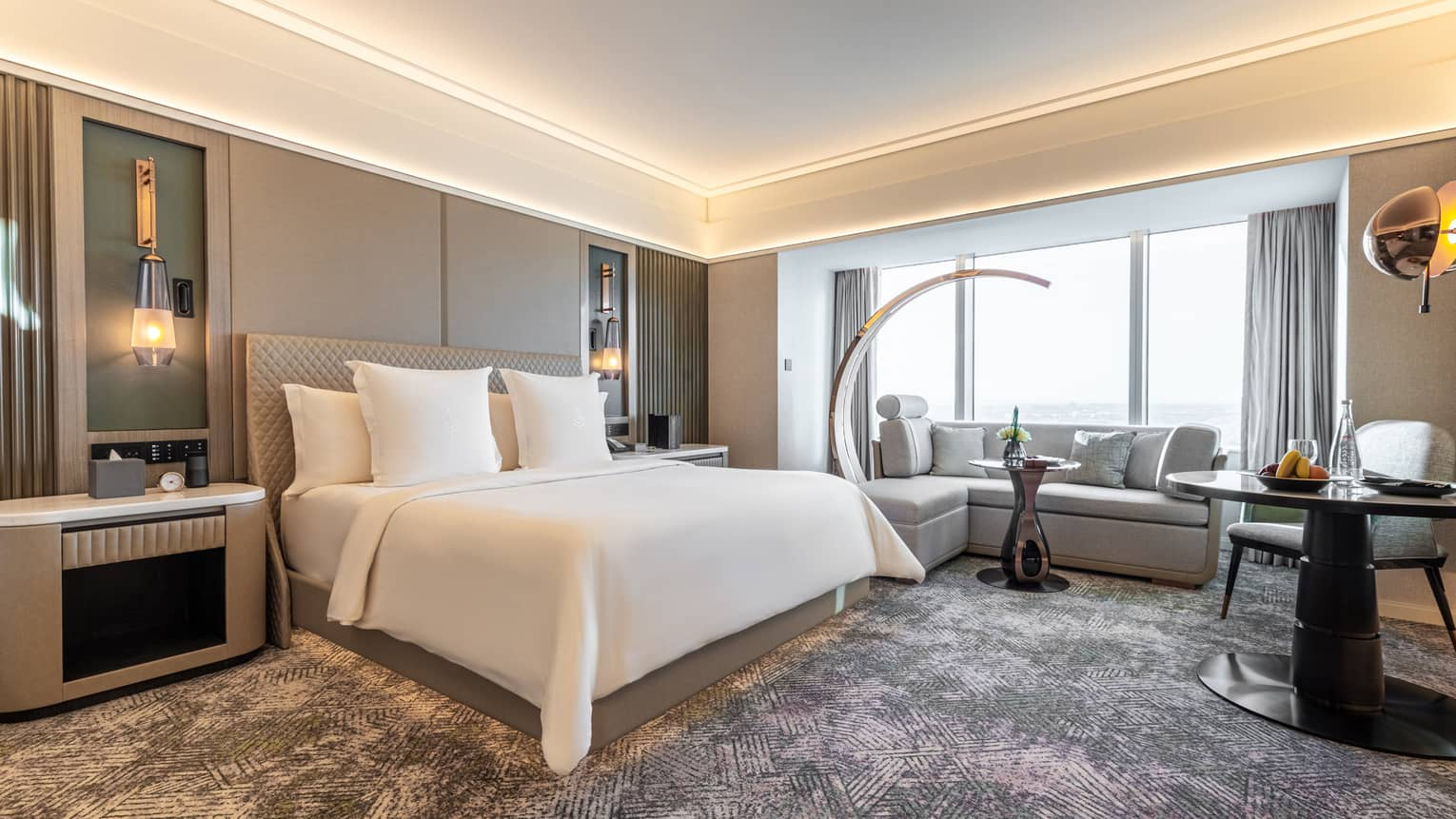 Hotel room with illuminated ceiling, grey walls and carpeting, white king bed, grey sofa and curved floor lamp