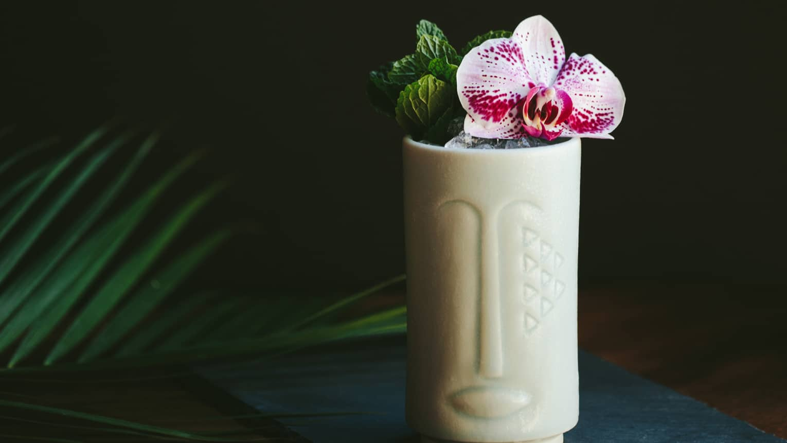 The Talisman cocktail in a tiki shaped glass with fresh flowers as a garnish