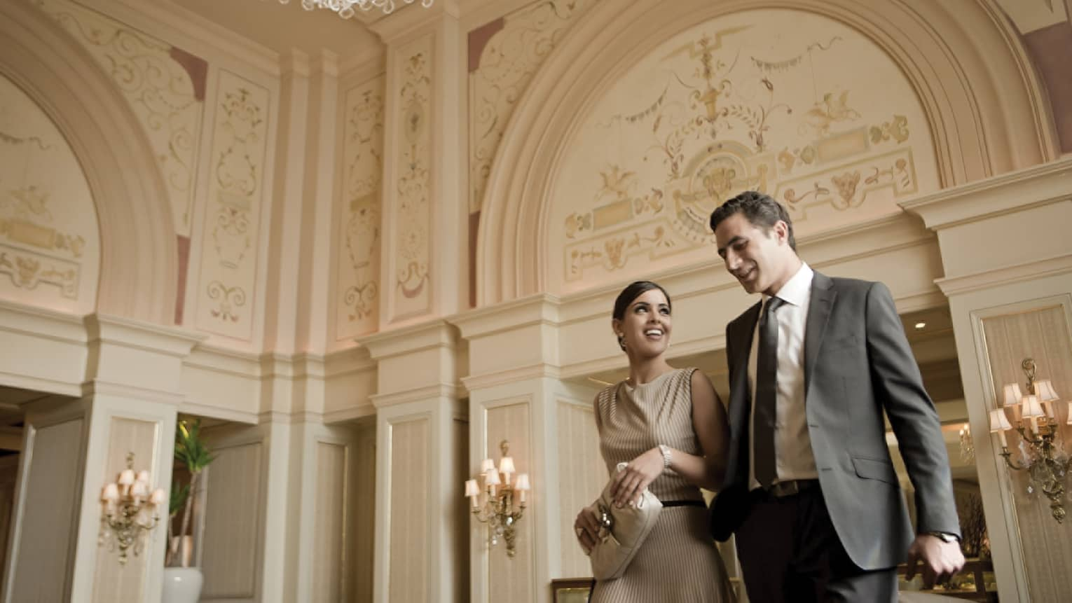 Smiling woman and man in business attire walk through hotel lobby