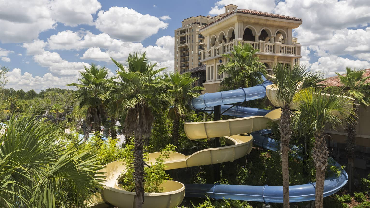 Building over winding outdoor water slide, palm trees