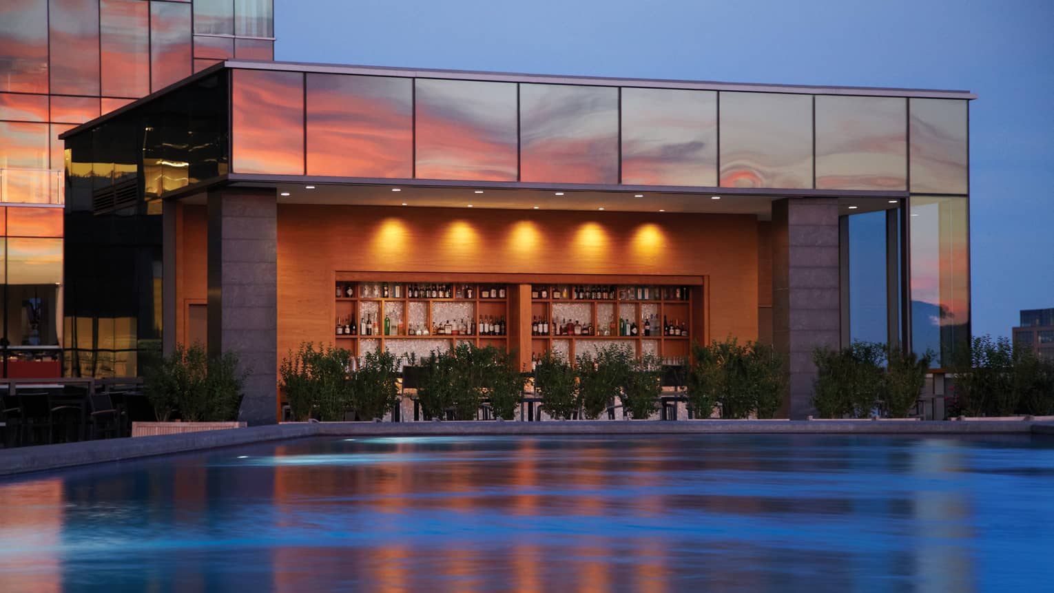 Illuminated swimming pool, wood bar and liquor displays under glass building exterior at sunset