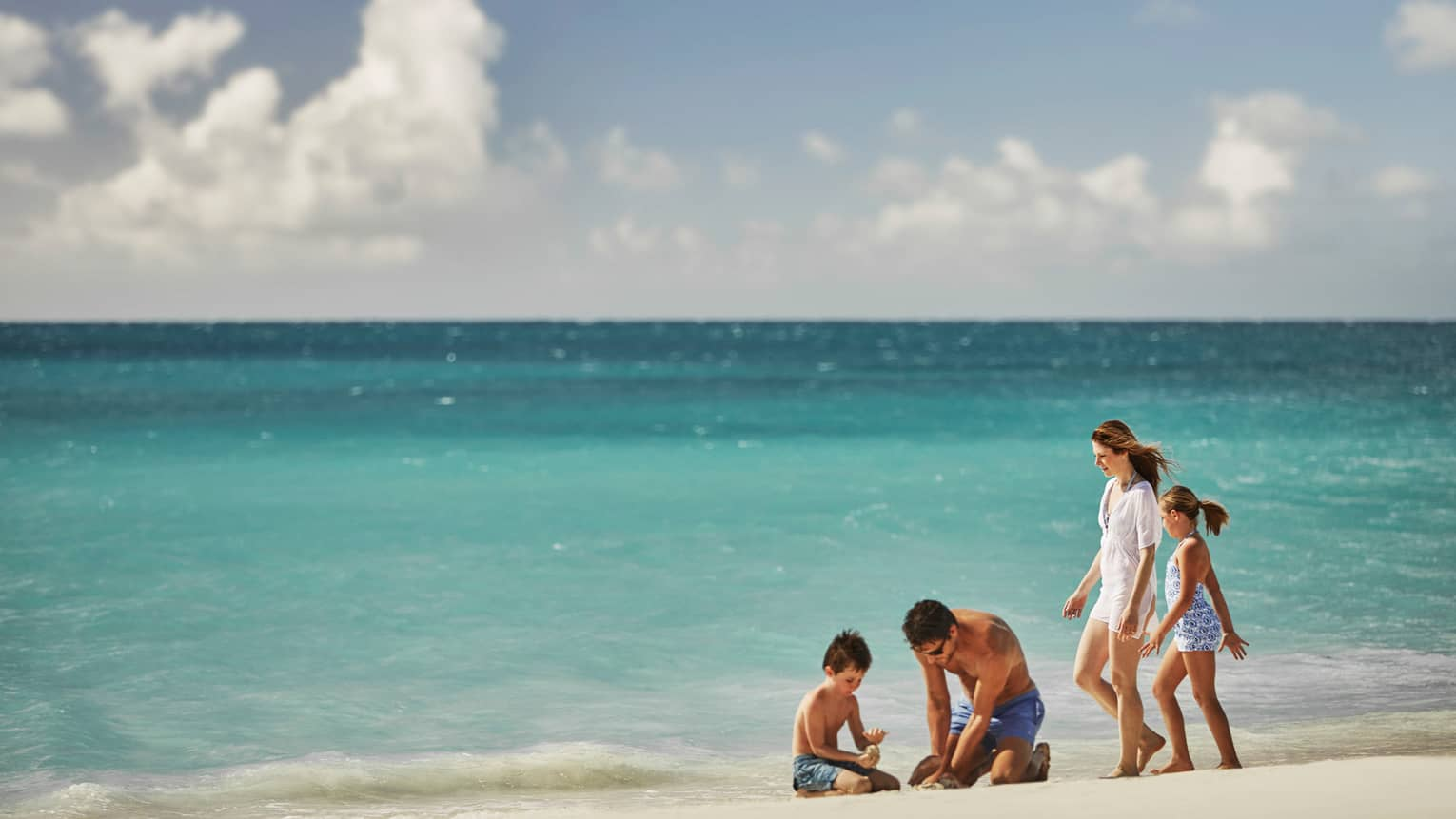 Man and little boy dig in sand while woman and young girl stand beside them on sunny sand beach by ocean