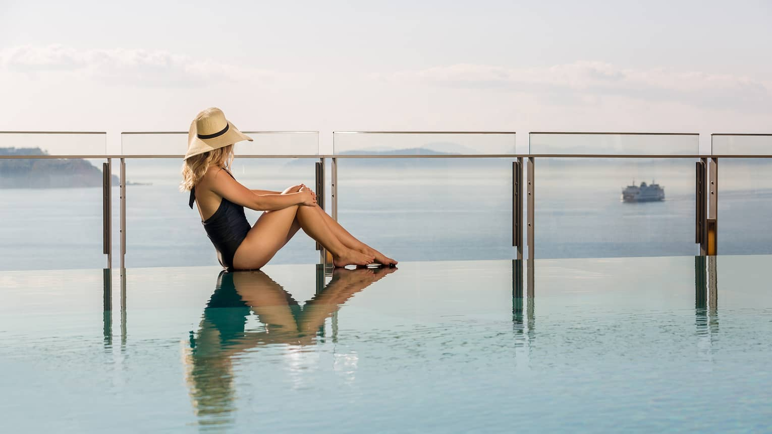 Woman in swimsuit, sunhat sits on pool deck in front of glass barrier, bay views