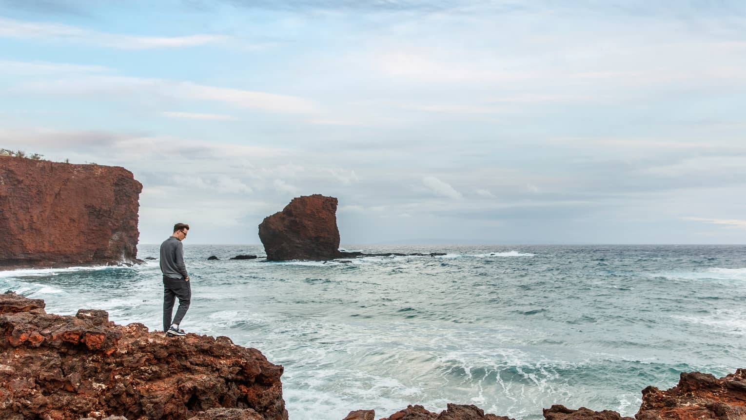 Man walks along brown rocks, looks down into ocean