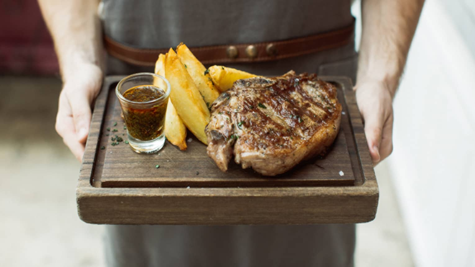 a 400-gram rib eye is served with chimichurri sauce and potato wedges