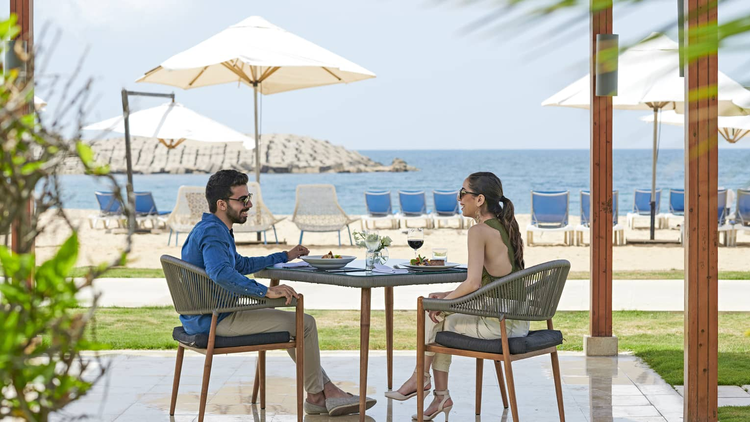 Smiling couple dines at patio table on private pergola near white sand beach