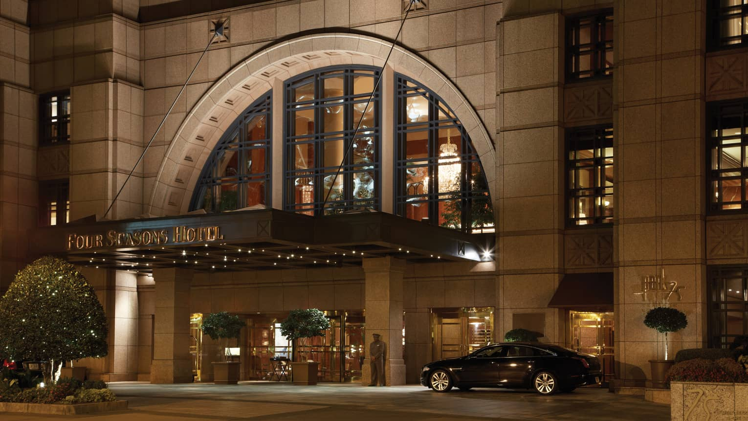 Black car beside arched doorway at front entrance, Four Seasons Hotel sign at night