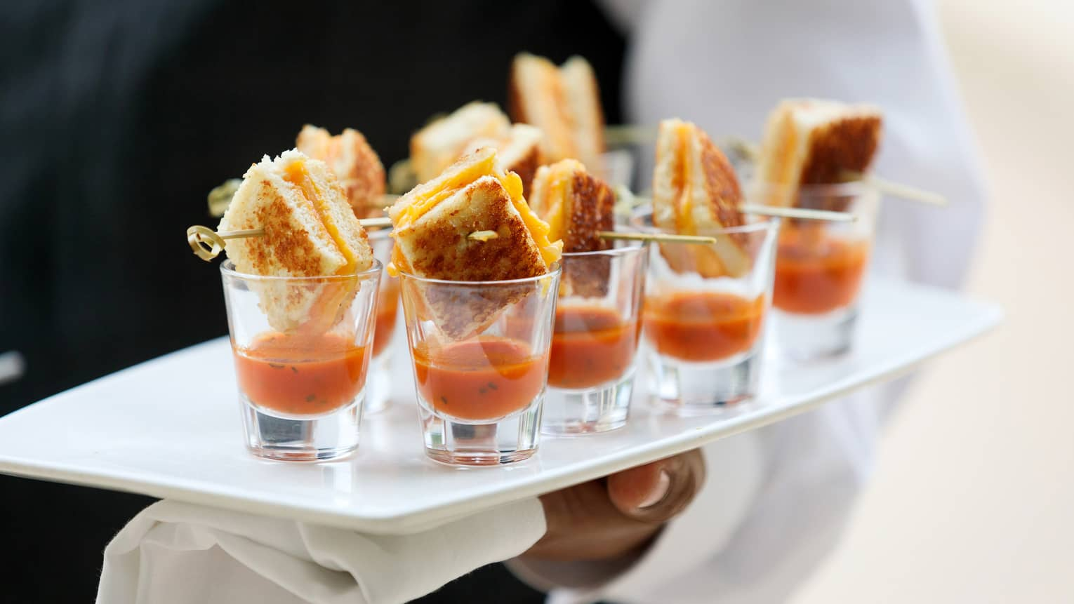 Close up of hotel staff holding platter with tomato soup and small grilled cheese sandwiches in shot glasses