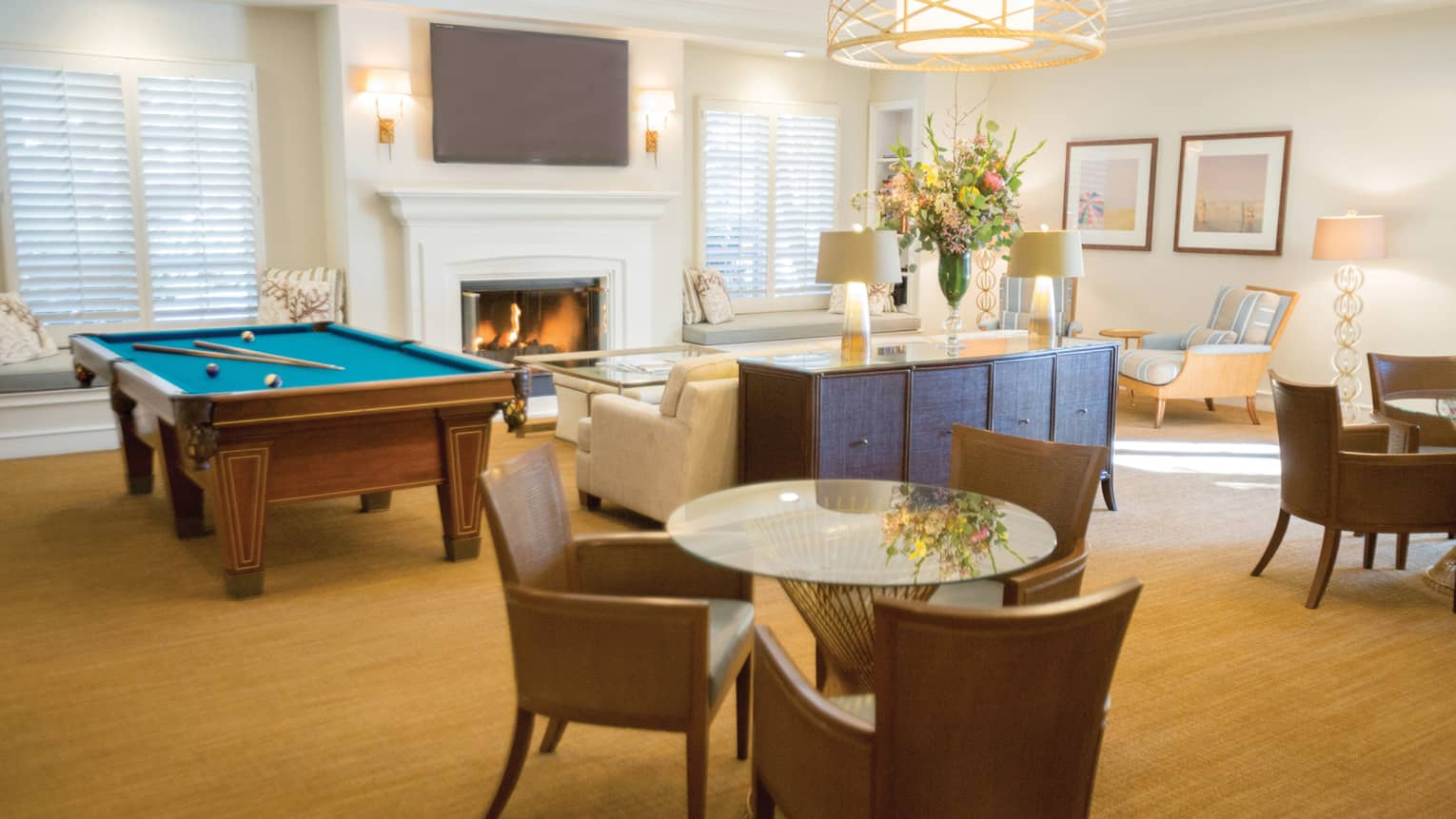Hotel recreation lounge with pool table, fireplace and sofa, round glass tables with chairs