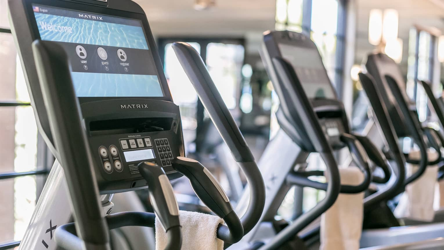 Close-up of Matrix cardio machine screens and handles in a row