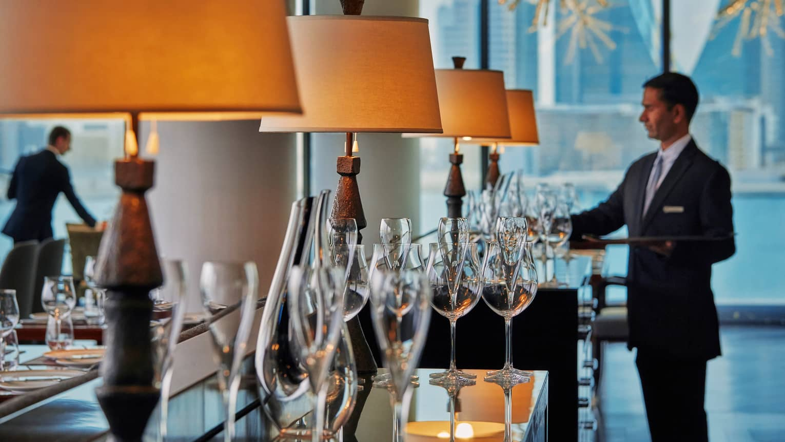 CUT by Wolfgang Puck restaurant sideboard lined with tall, shaded wooden lamps and champagne flutes, staff in background