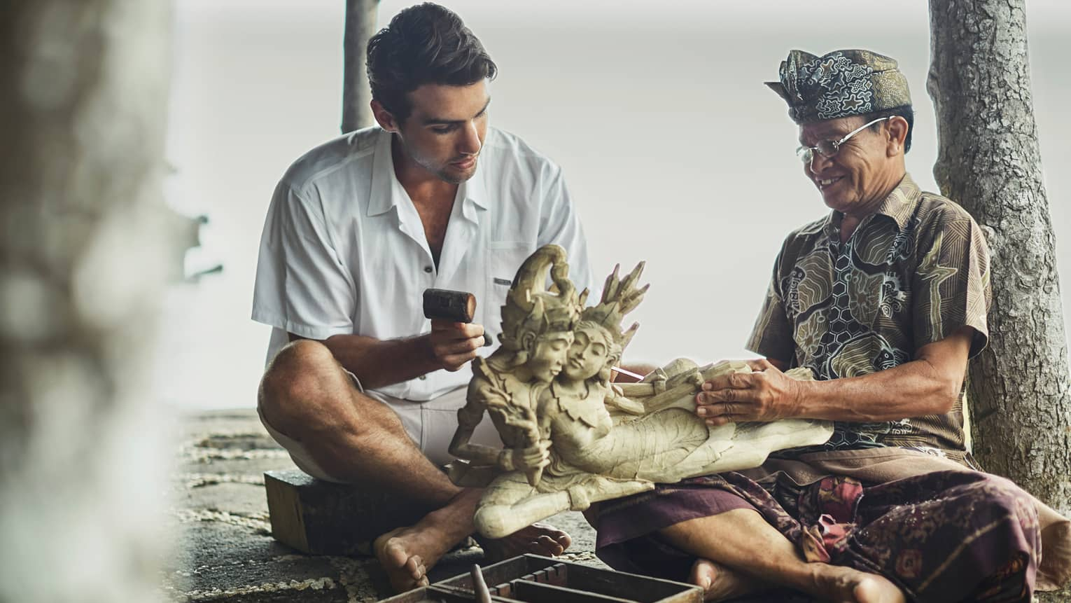 Man in white shirt sitting on mat with man in headdress and native costume holding carving