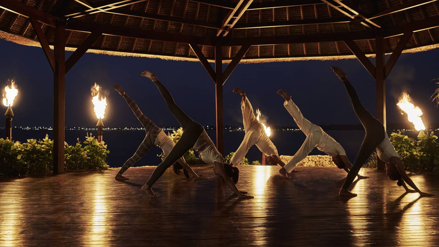 Guests with their legs outstretched, participating in yoga on a fire-lit pavilion