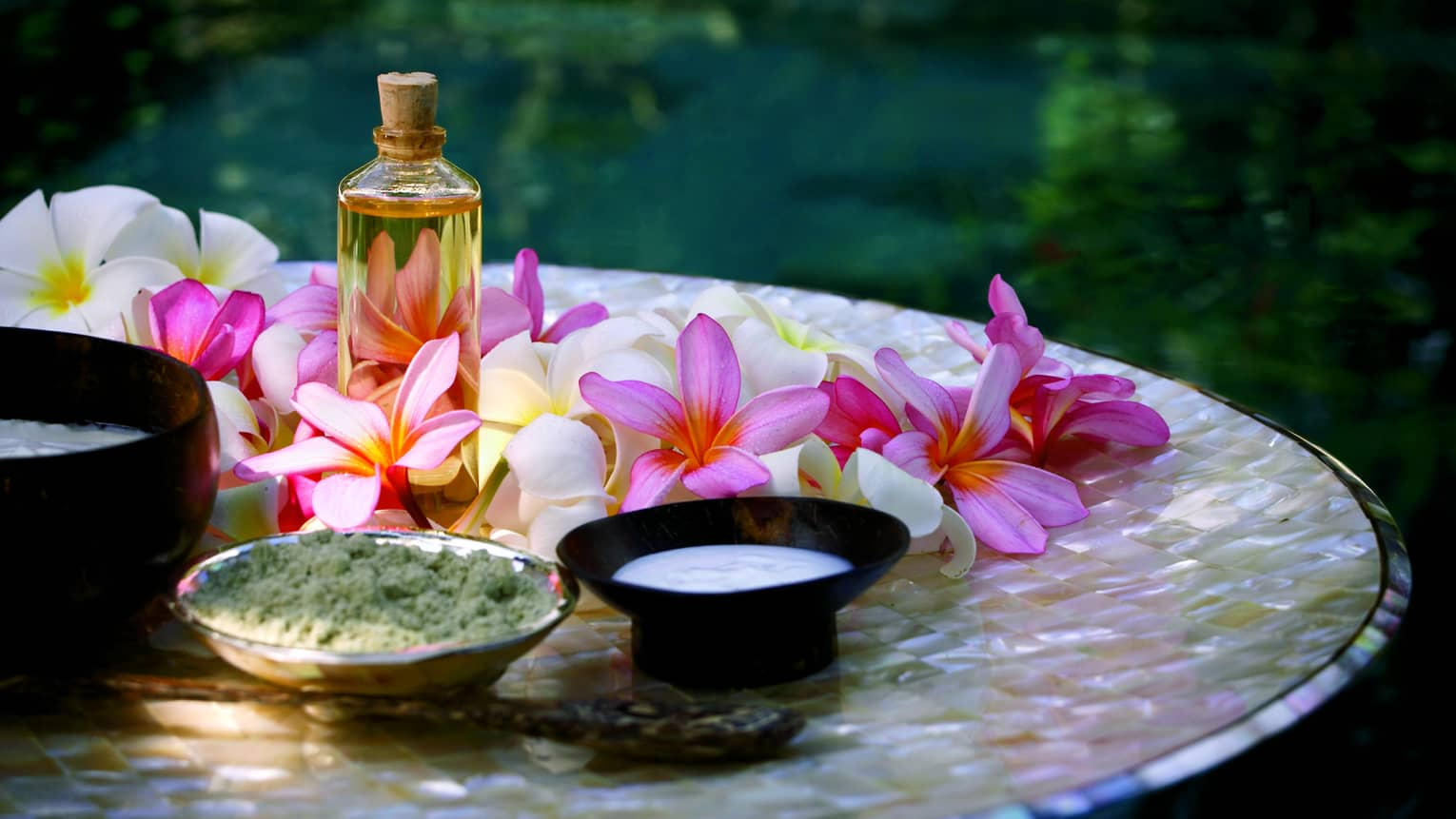 Spa tray with fresh pink and white flowers, glass bottle with oil and cork, small bowls of salt and lotion