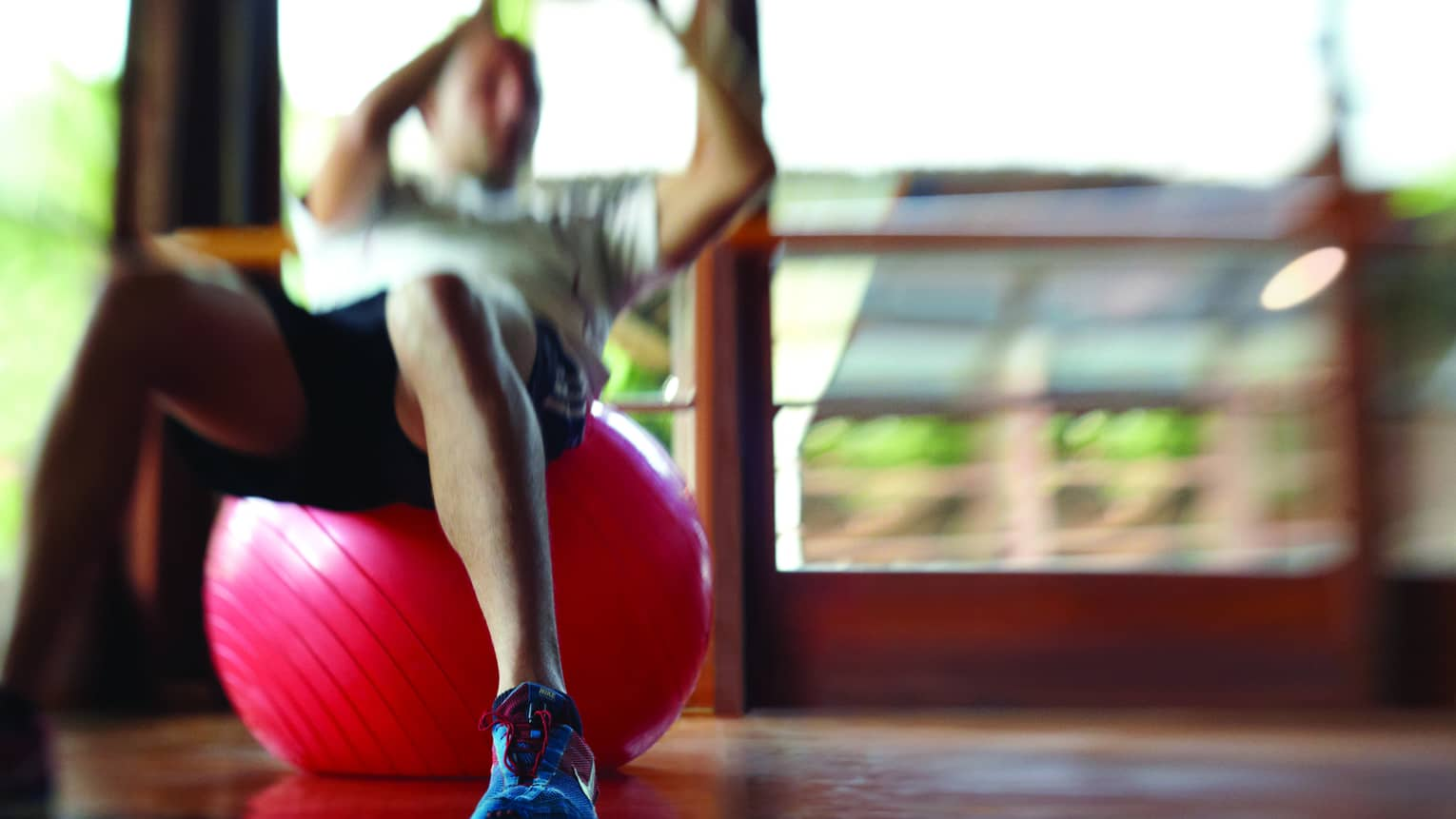 Blurry image of man in shorts and T-shirt doing sit-up on red pilates ball on wood floor