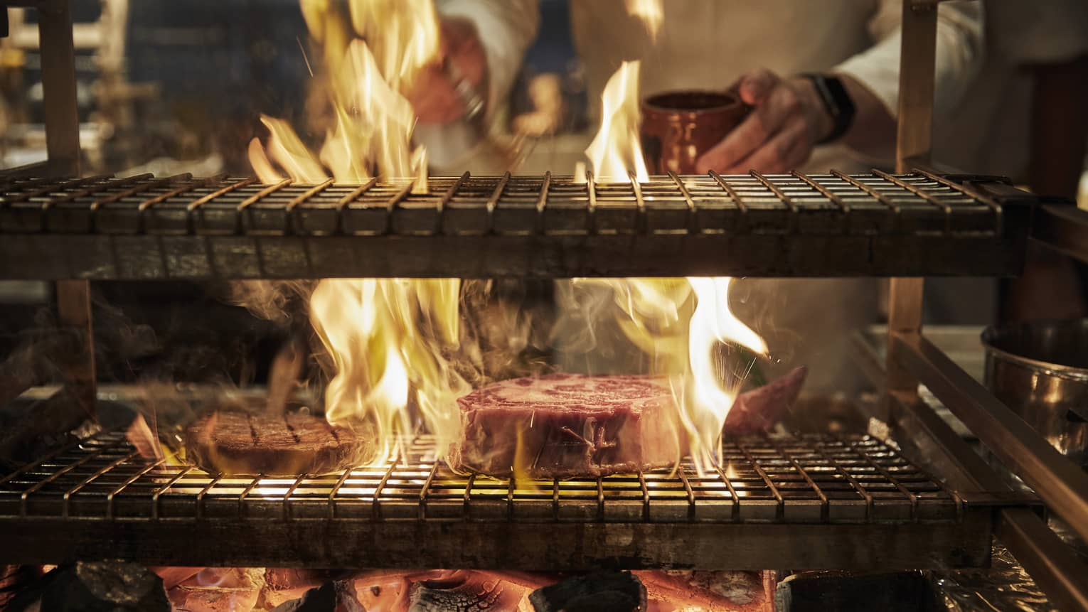 A Zuma chef grills on an open flame