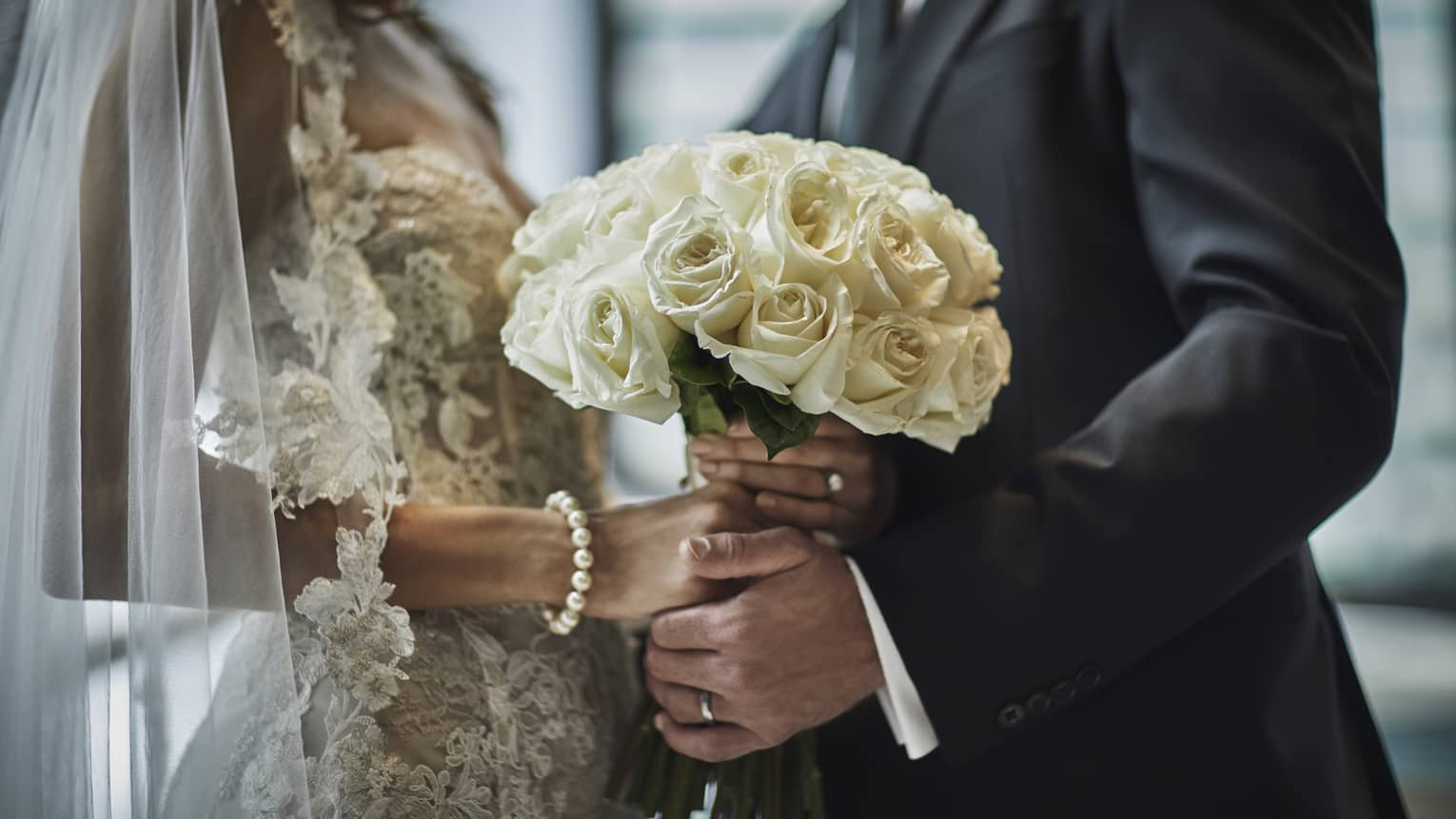 A close up of a bride in a lace gown and a groom in a gray suit hold the bride's bouquet of white roses together.