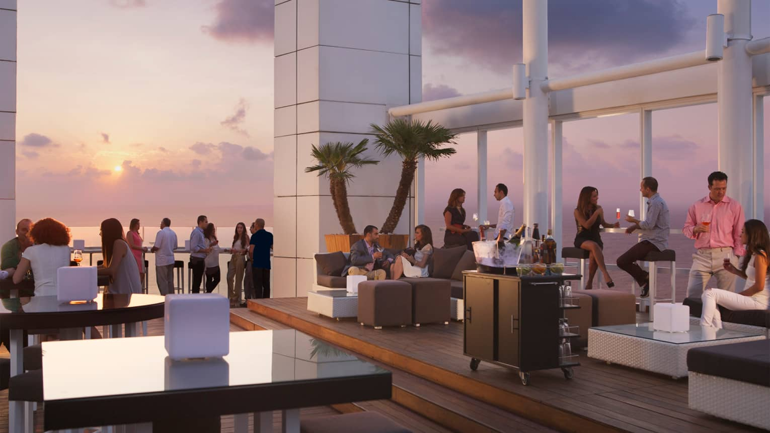 Crowds mingle on rooftop patio on wicker sofas and stand alongside rail as sun sets in background