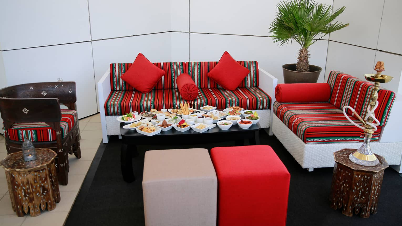Close-up of small black table with more than a dozen white dishes with mezze appetizers and snacks, colourful striped sofa