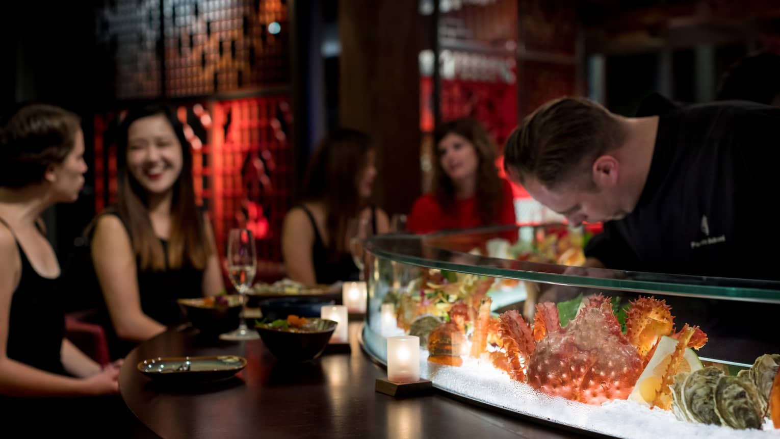 Chef leans down behind round glass seafood bar where smiling women sit at bar
