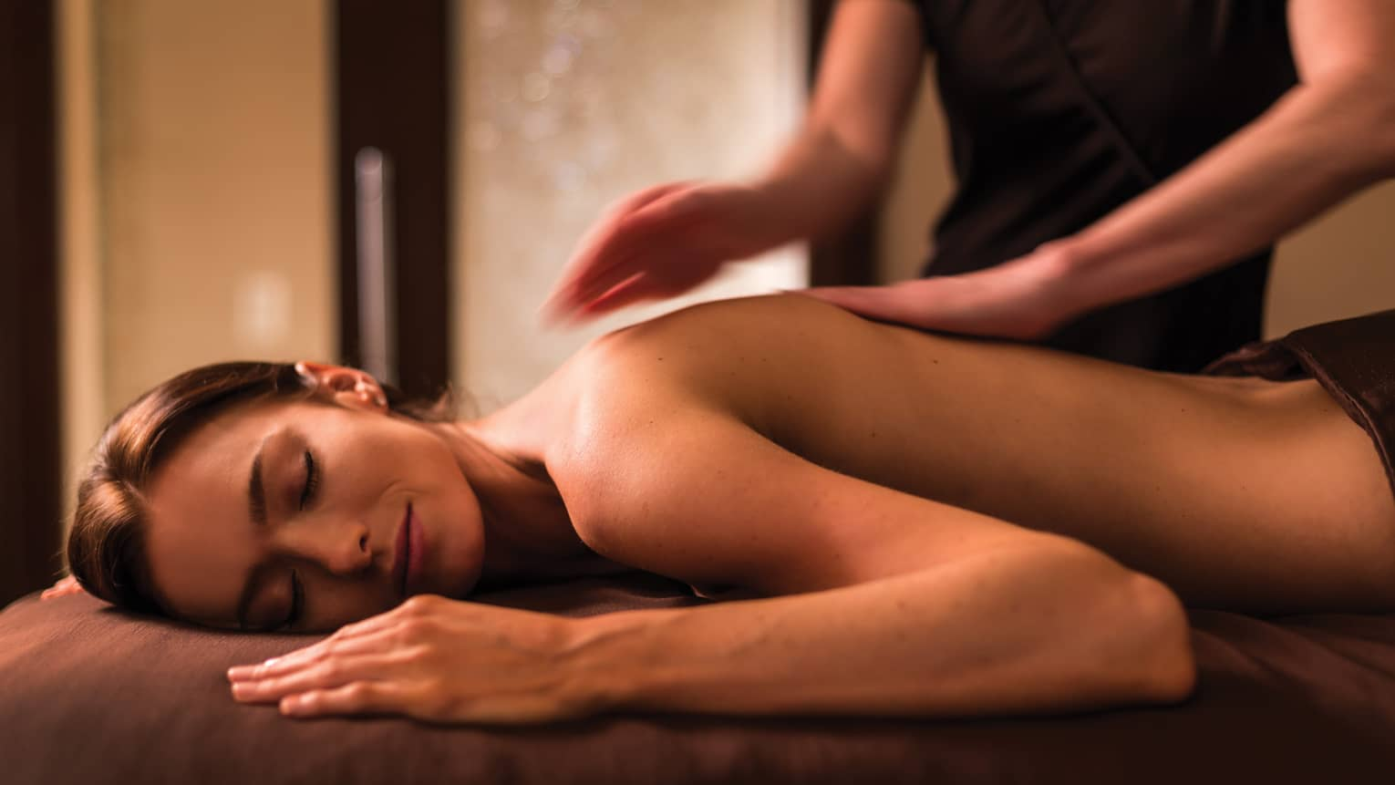 Woman with eyes closed lies on massage table in dimly-lit spa room
