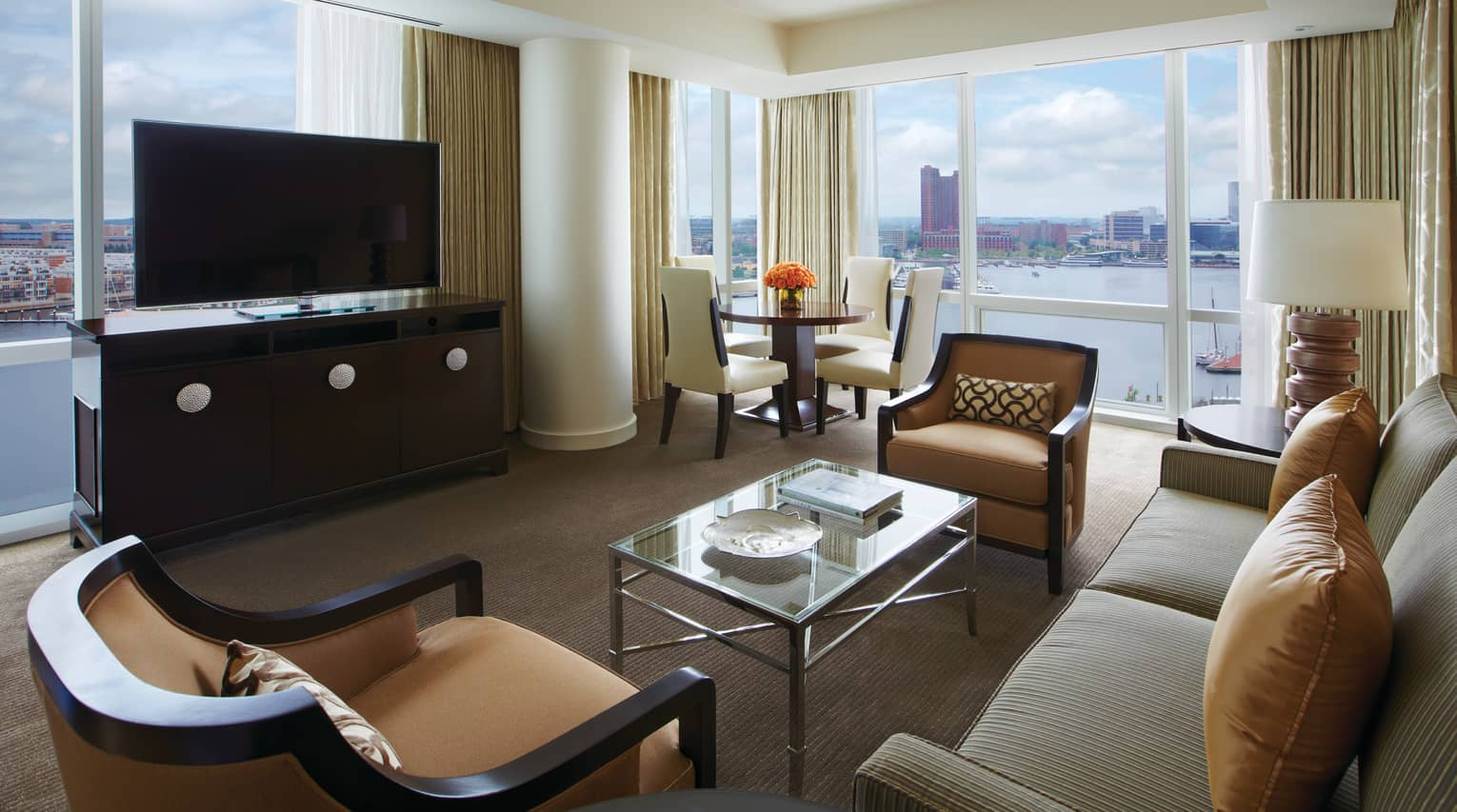 Harbour Suite loveseat, armchairs, dresser and TV in front of window overlooking water