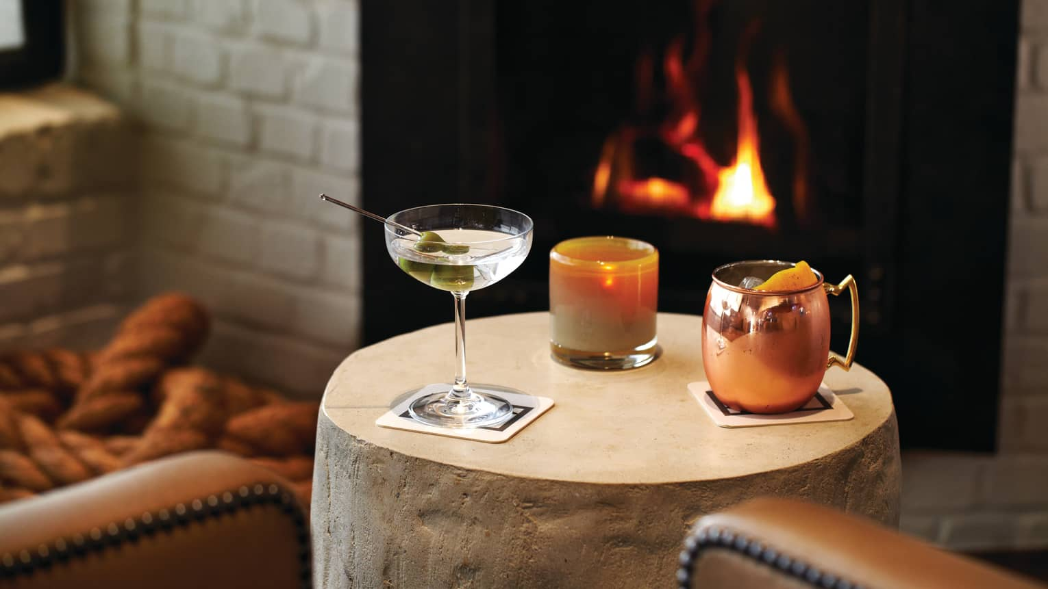 Martini glass, cocktail and copper mug on small round table in front of fireplace