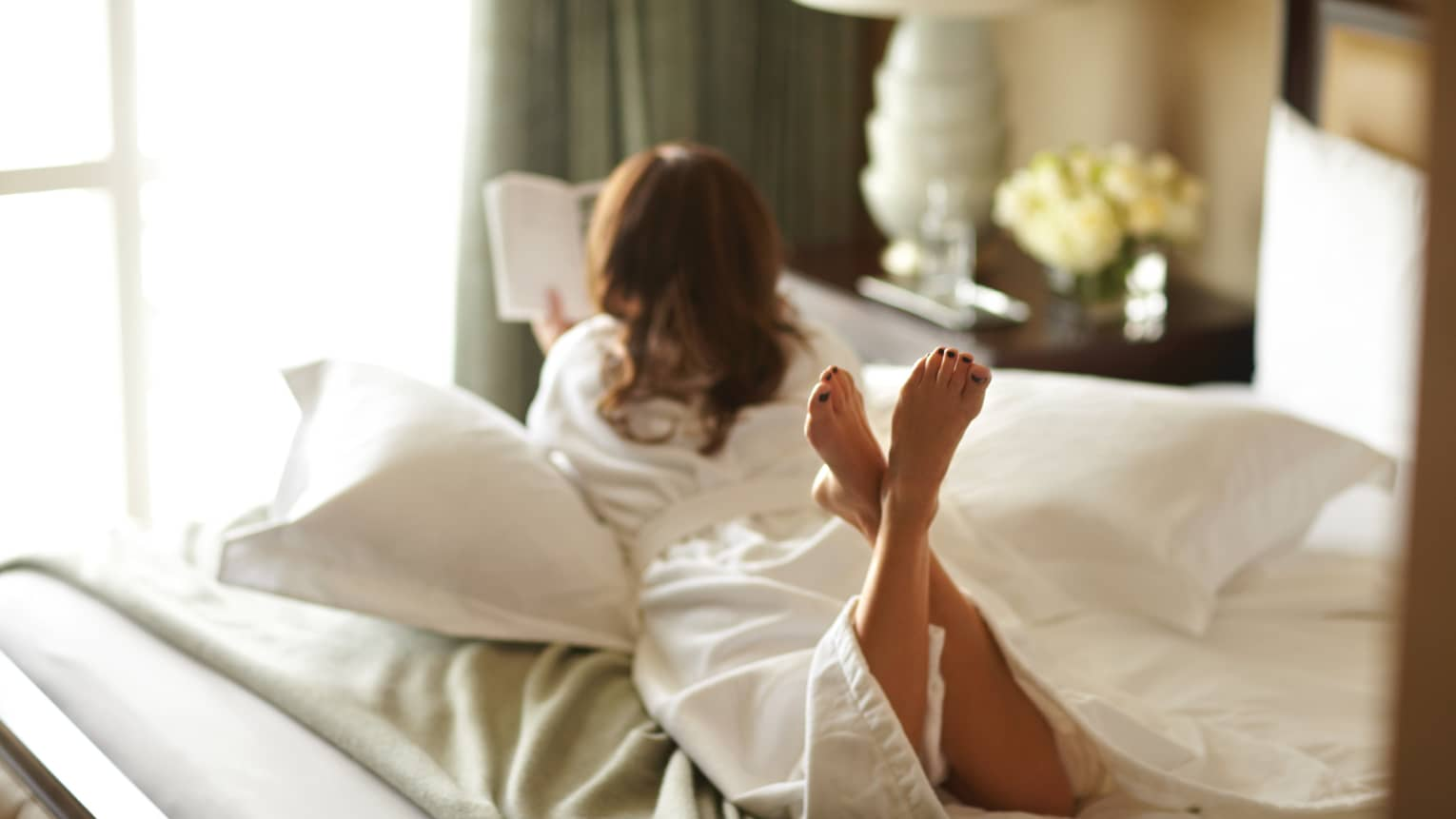 Woman in white bathrobe reads book, lies on bed with legs crossed