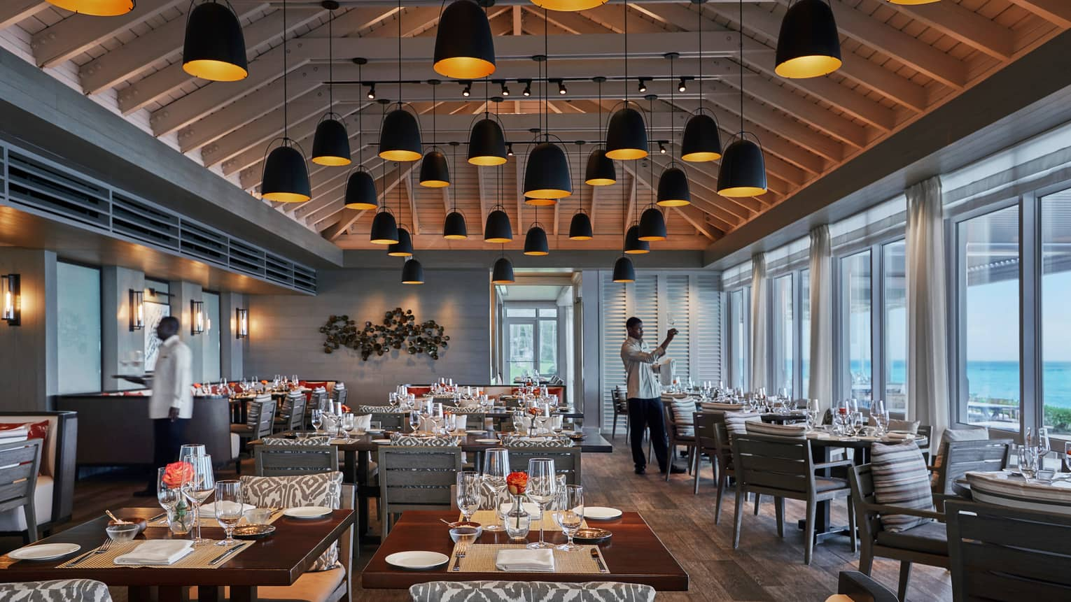 Servers set tables in spacious Dune dining room with soaring ceilings, lights hanging from beams