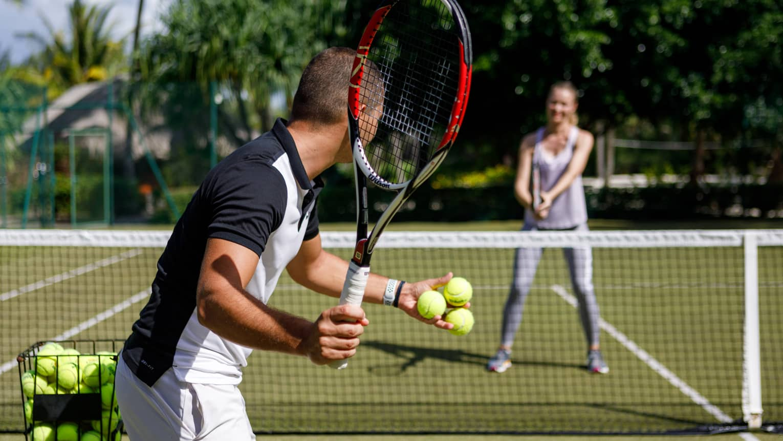Couple playing tennis on court, man prepares to serve tennis balls to woman ready to swing
