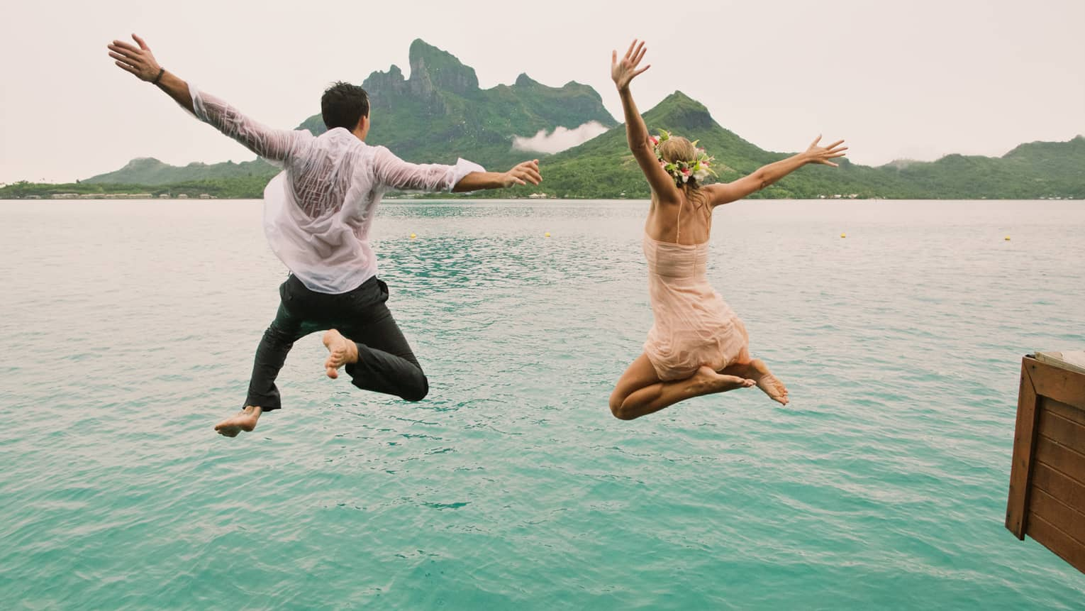 Woman and man in mid jump into turquoise lagoon