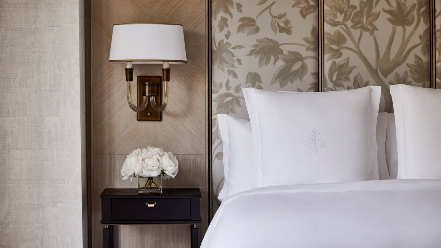 Deluxe Accessible Room close-up of bed, white pillows, beige headboard, small reading lamp on wall, white flowers on nightstand