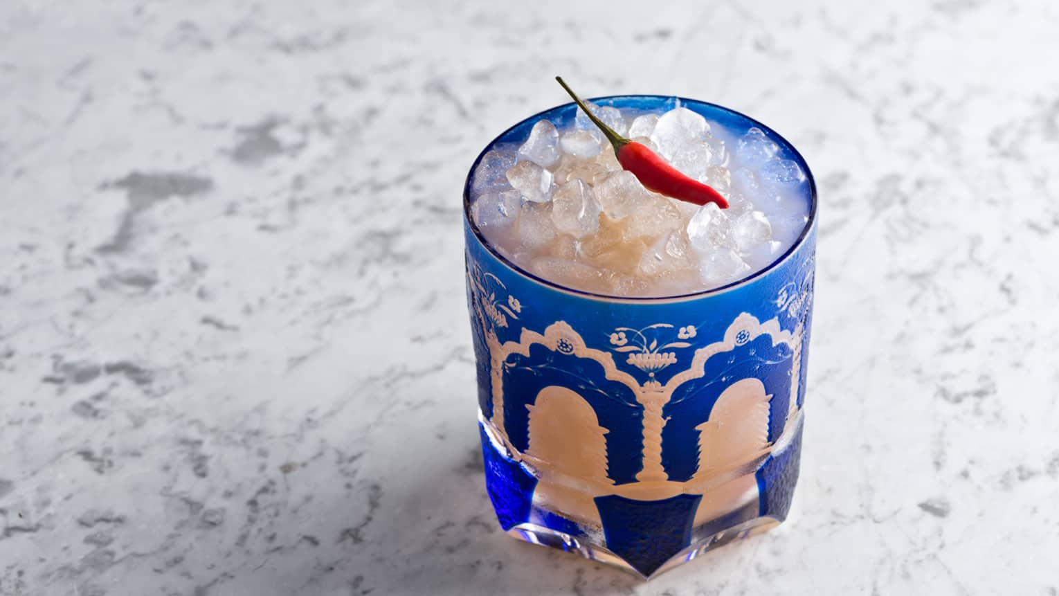 Kalocsai Paprika cocktail on ice in blue glass, small red hot pepper garnish