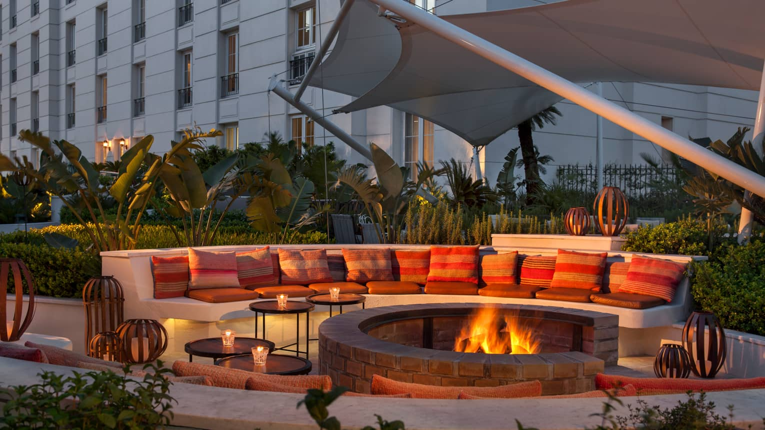 Large curved white bench with cushions around outdoor fire pit with flames at dusk